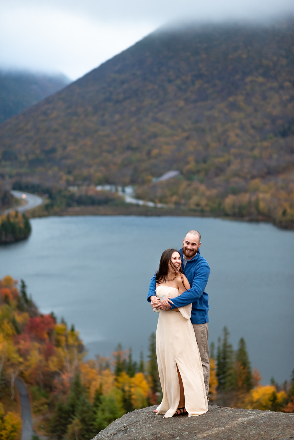 couple smiling and groom guy keeping girl warm wrapping her in a hug from behind. the white mountains of new hampshire are behind them