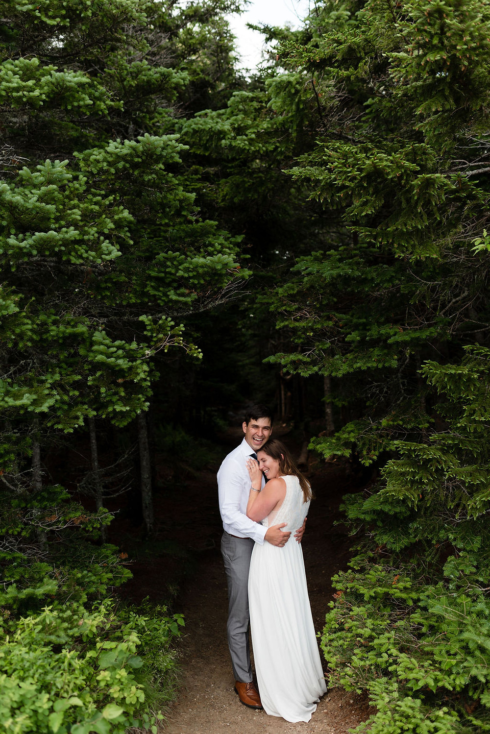 bride snuggled into groom's chest, the groom is smiling really big at the camera. they're standing at the end of the mount willard trail