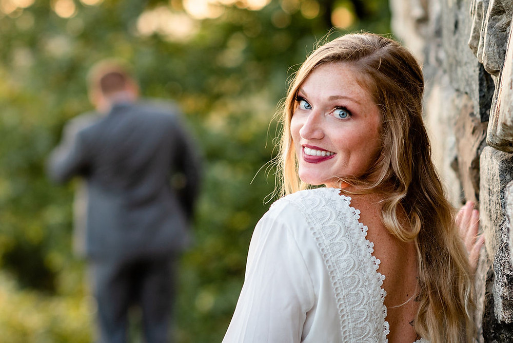 photo is taken right before a bride and groom's first look. the groom has his back to the camera in the distance. the photo focuses on the bride, who is looking over her shoulder at the camera smiling. she is resting on a stone wall which belongs to Wright's Tower at Middlesex Fells reservation