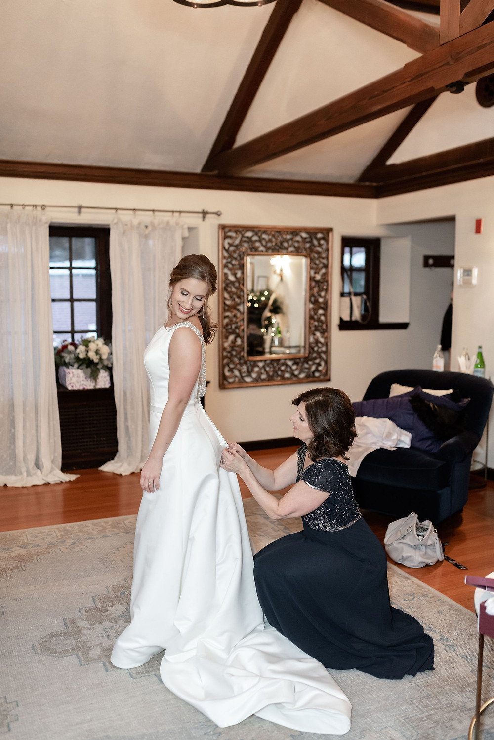 mom buttoning bride's dress before wedding ceremony