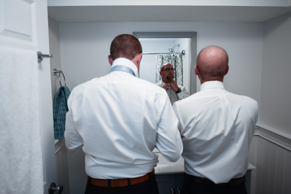 groomsmen getting ready in the bathroom mirror