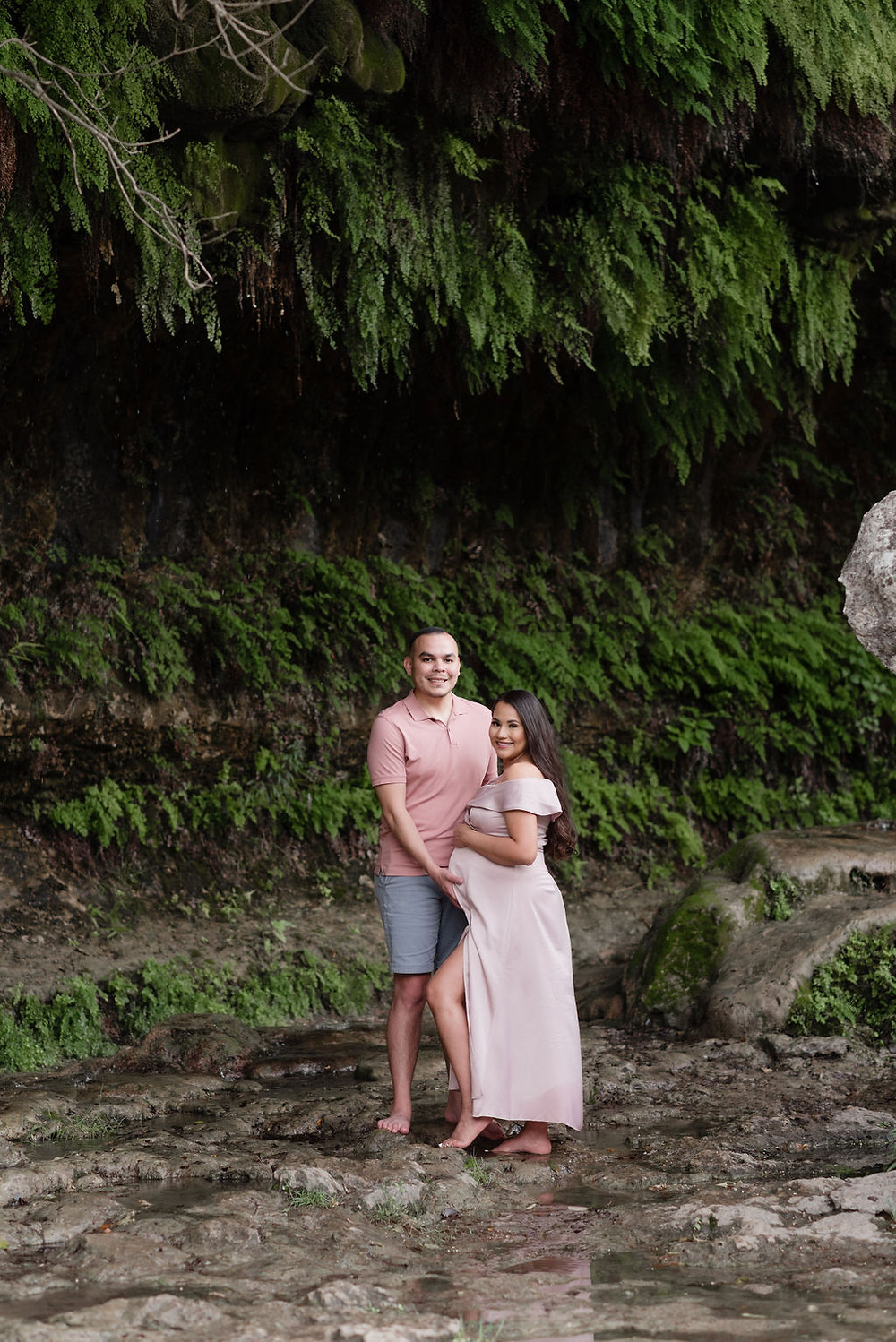 hidden gem at bull creek. there is a mossy cave that drips water behind a huge rock. excellent place to take photos that are shadowy and dramatic. mom and dad smile looking at camera for their maternity session. dad has hand on mom's pregnant belly