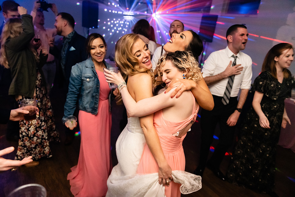 bride and bridesmaids dancing at wedding reception with disco ball