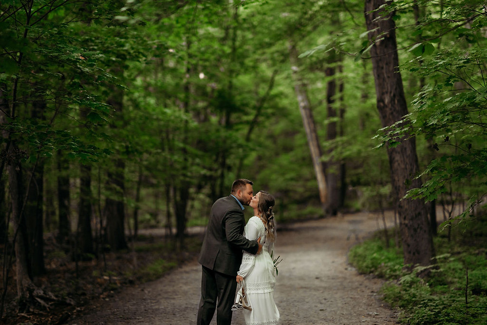 bride and groom standing in middle of trail kissing while on their elopement