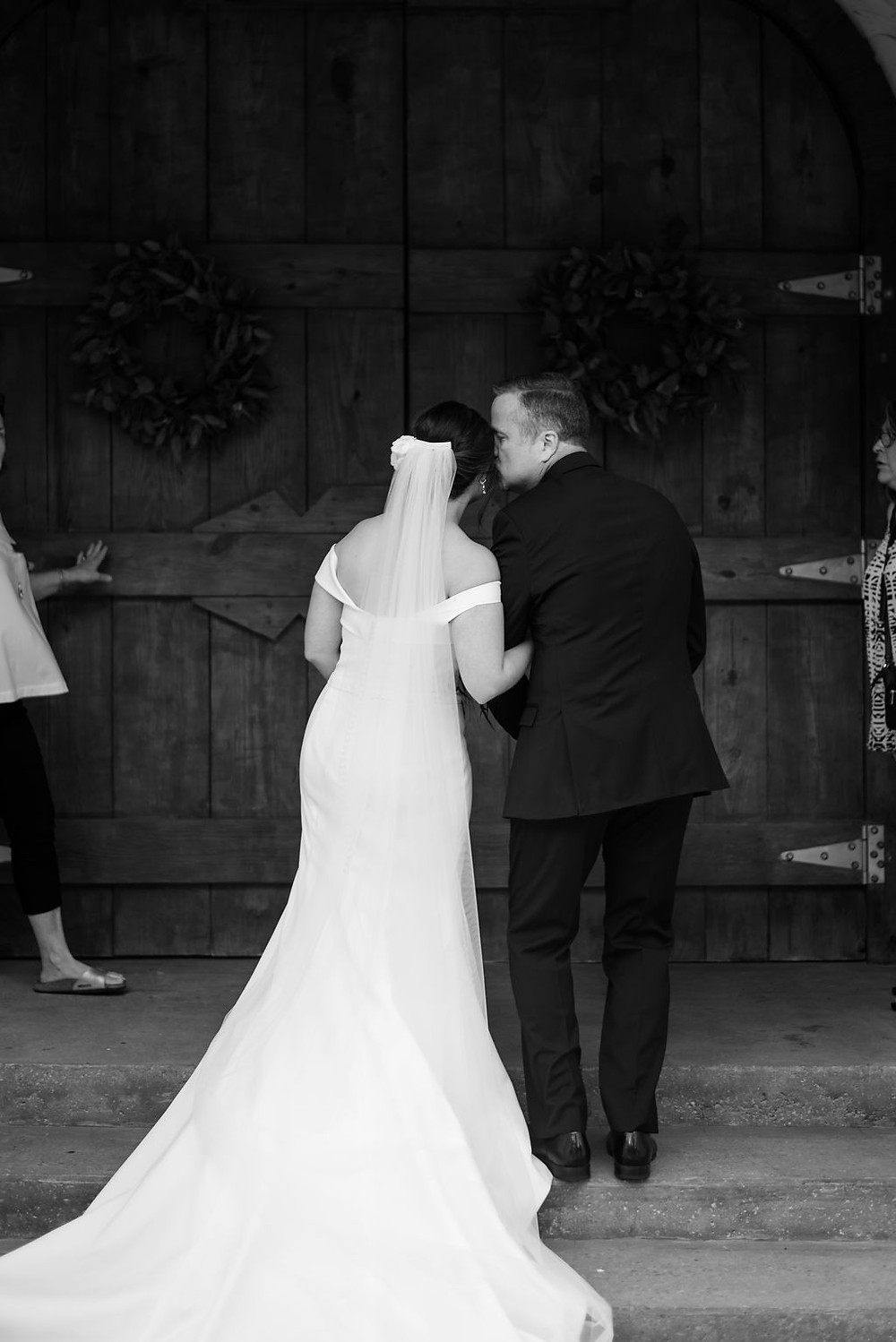 bride and dad share a kiss before chapel doors open to wedding ceremony at villa antonia
