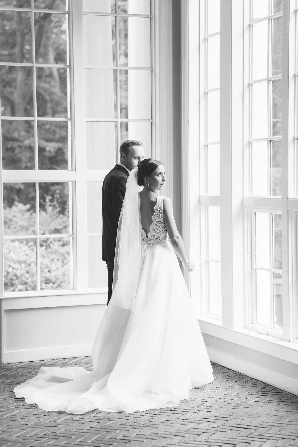black and white candid moment of couple in the reception area of tupper manor