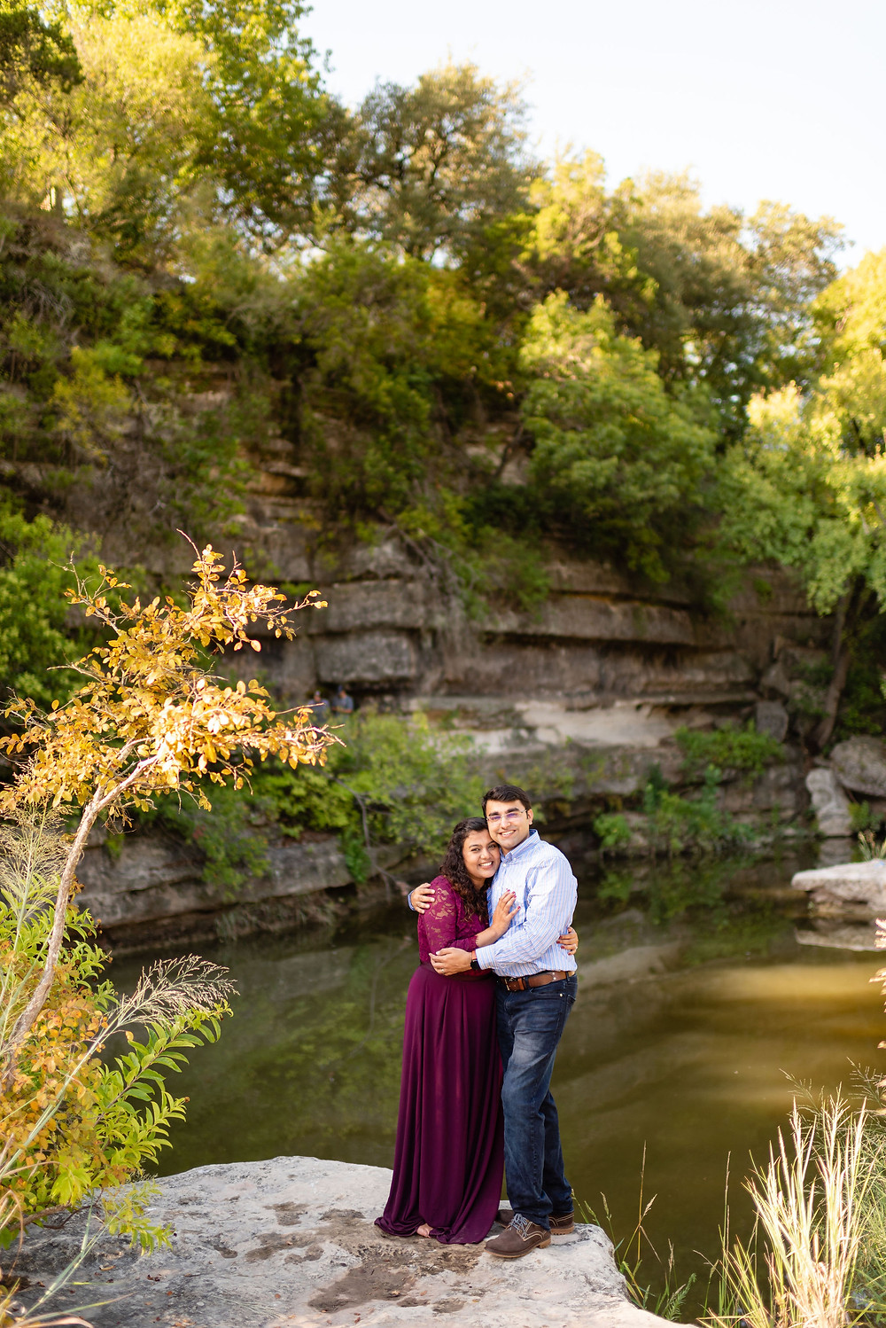 adventurous landscape in austin at bull creek. girl and guy smile at camera at edge of water with large rockwall behind them