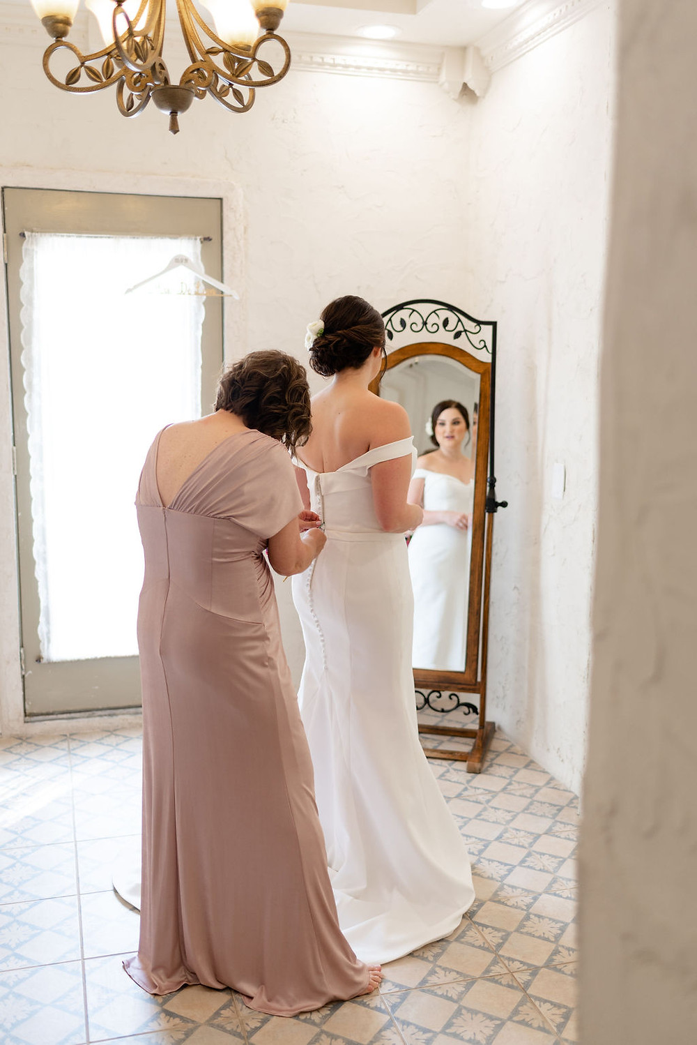 mom heling bride into wedding dress in the bridal suite of villa antonia