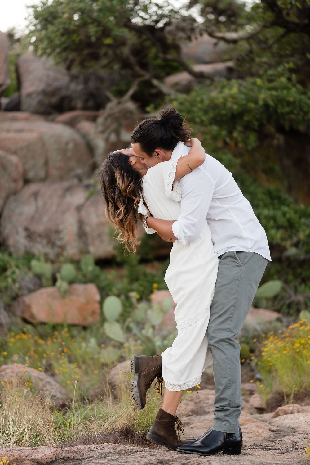 guy holding girl in his arms kissing her neck