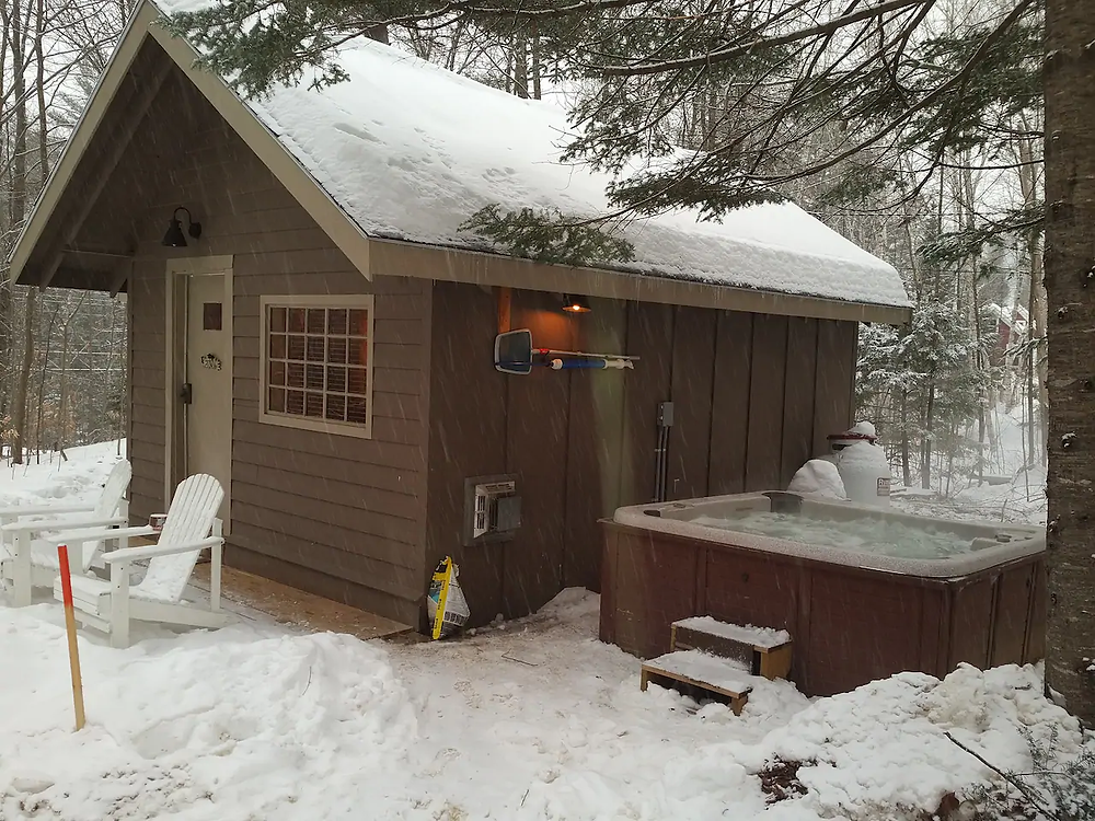 cozy cabin in the snow with hot tub