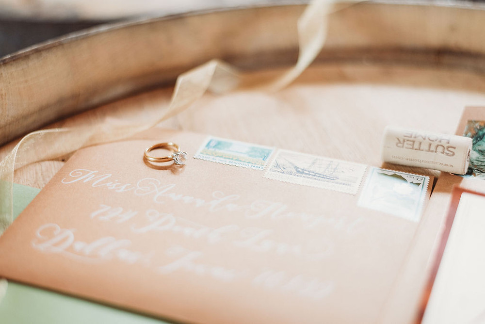 invitation suite from brown fox creative. brown envelope and green invitations. engagement ring, wine cork, and ribbon details. on a beer barrel