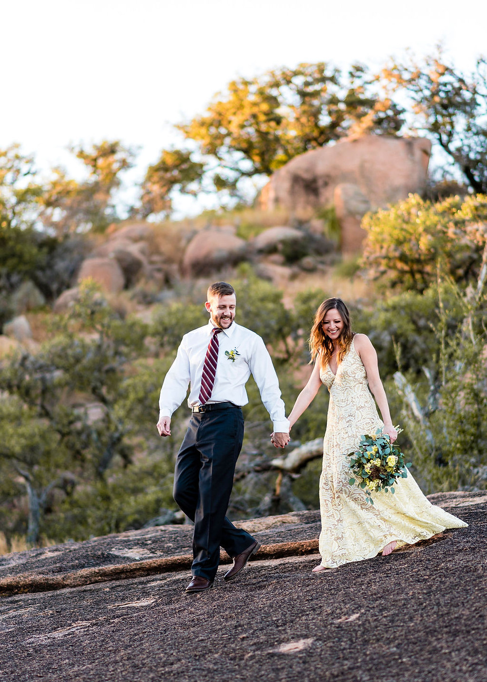 bride and groom holding hands smiling candidly while walking along boulder at enchanted rock during elopement