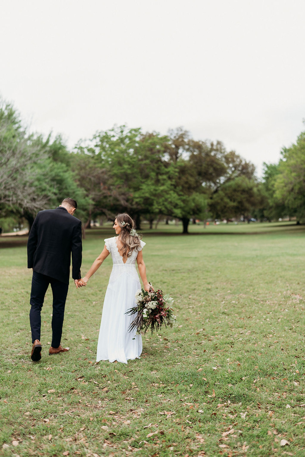 bride and groom hold hands and are walking away from the camera. bride hangs her bridal bouquet down to her side. They are small in the frame and you can see the field behind them. Austin elopement at festival beach next to lady bird lake