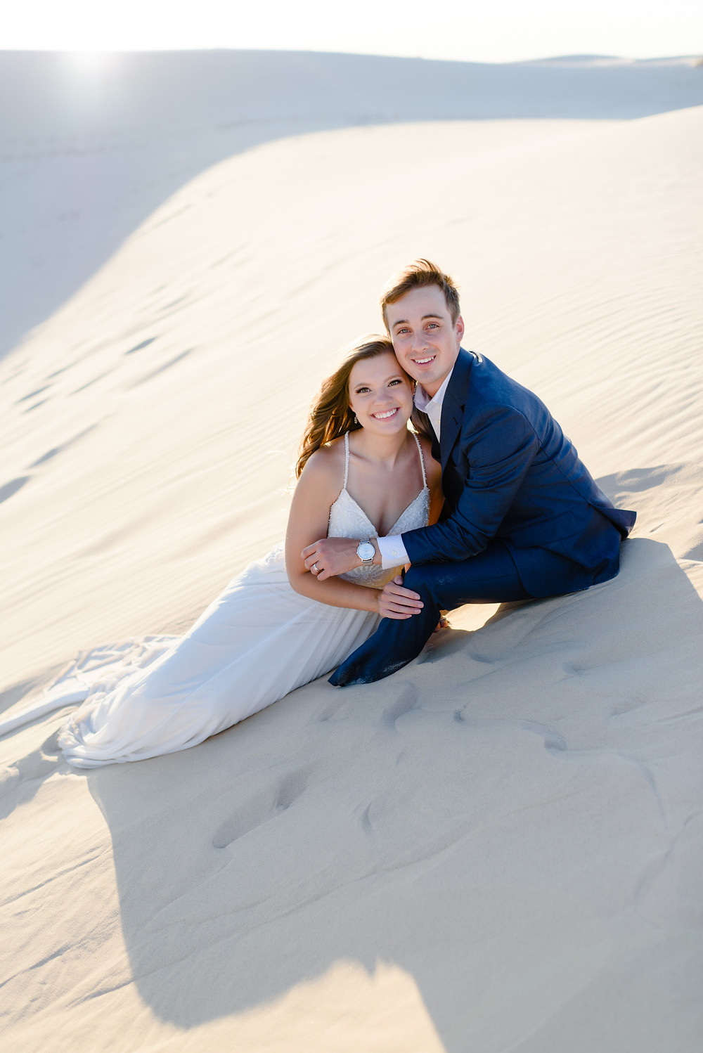 elopement in sand dunes with couple sitting in sand smiling at the camera