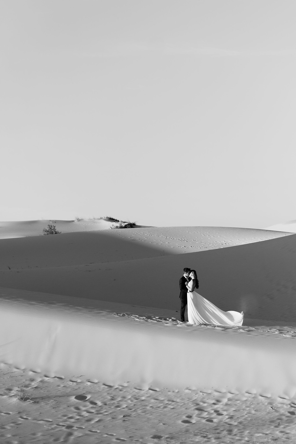 black and white heavily contrasted photo of the couple embracing during their elopement. the sun is setting so heavy shadows are cast on the side of the sandhills