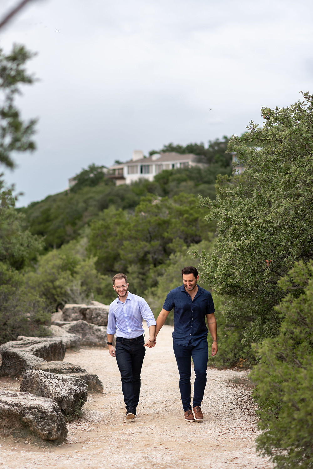 engagement photos at mount bonnell. couple walks along dirt path in between trees