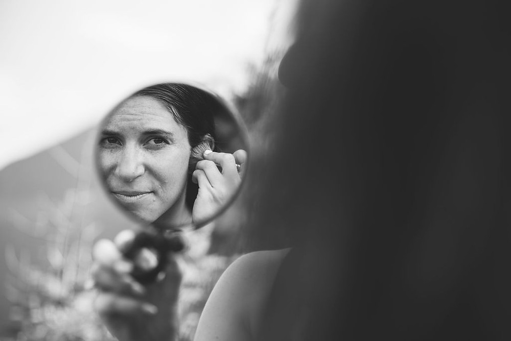bride doing makeup on top of mountain