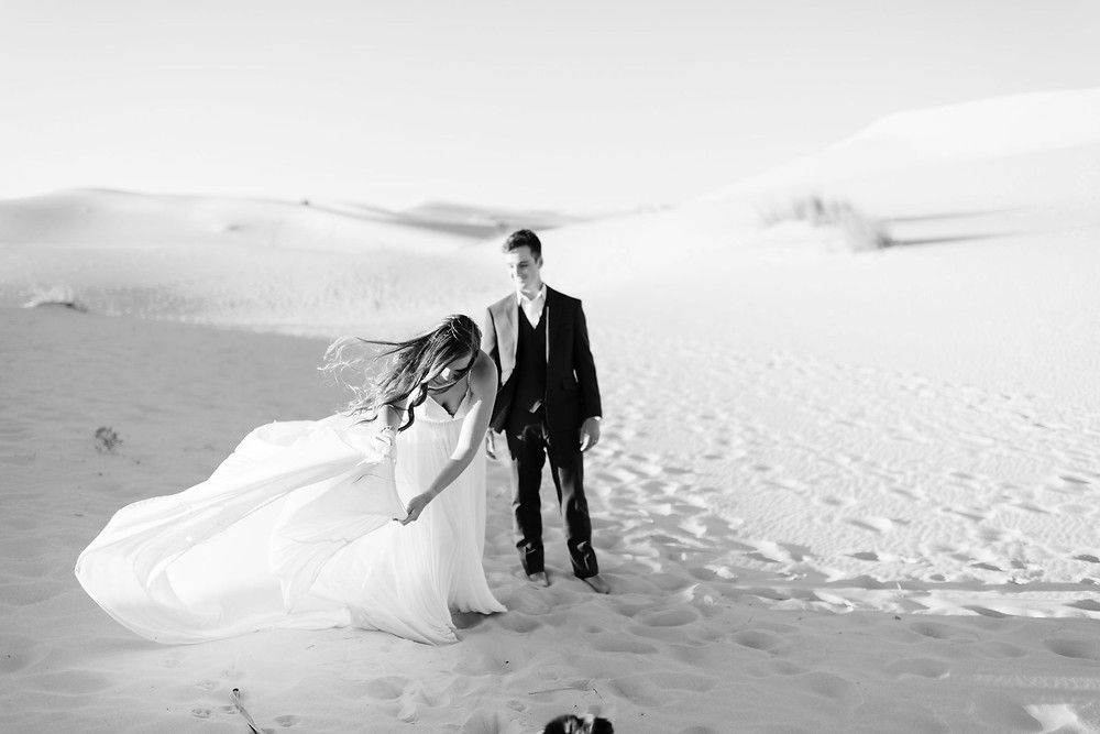 bride rearranges train of dress while the wind is blowing, which gives her a difficult time.