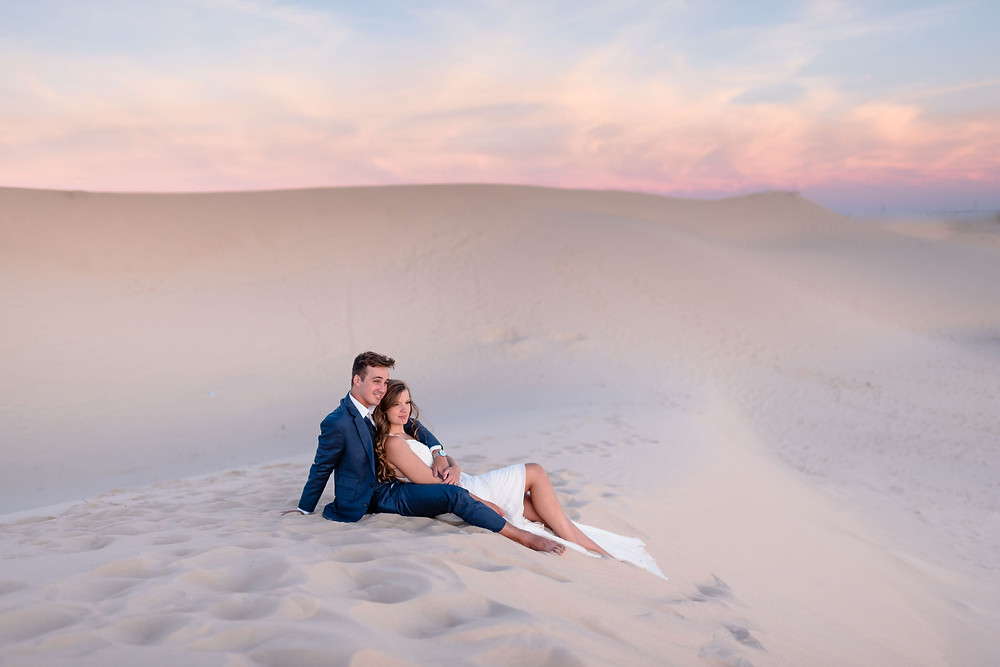 bride sits in between groom's legs on the sand hill. they are watching the sun set together. behind them you can see monahans sandhills landscape and a cotton candy sky from the sunset