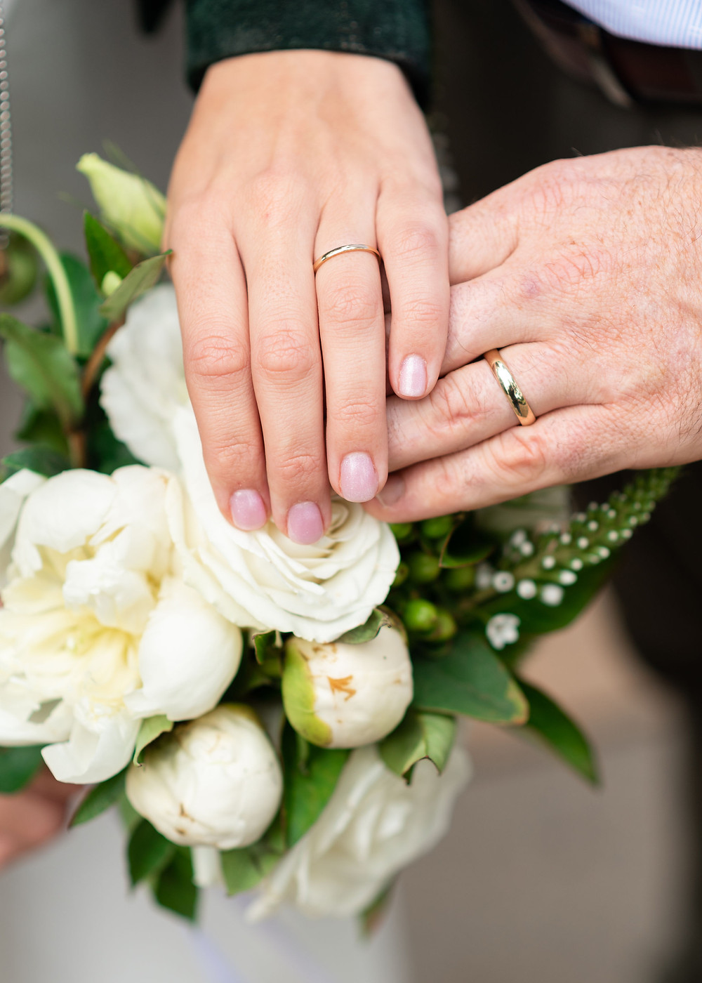 wedding bands on hands by flowers
