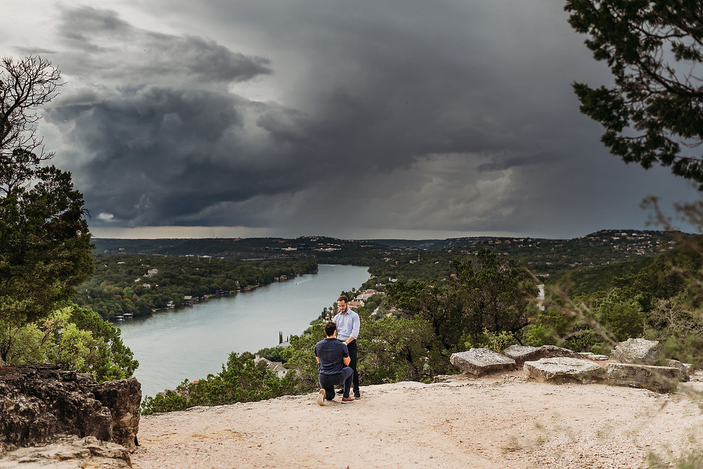 man proposing to boyfriend at mount bonnell in austin, texas with epic storm clouds in the background