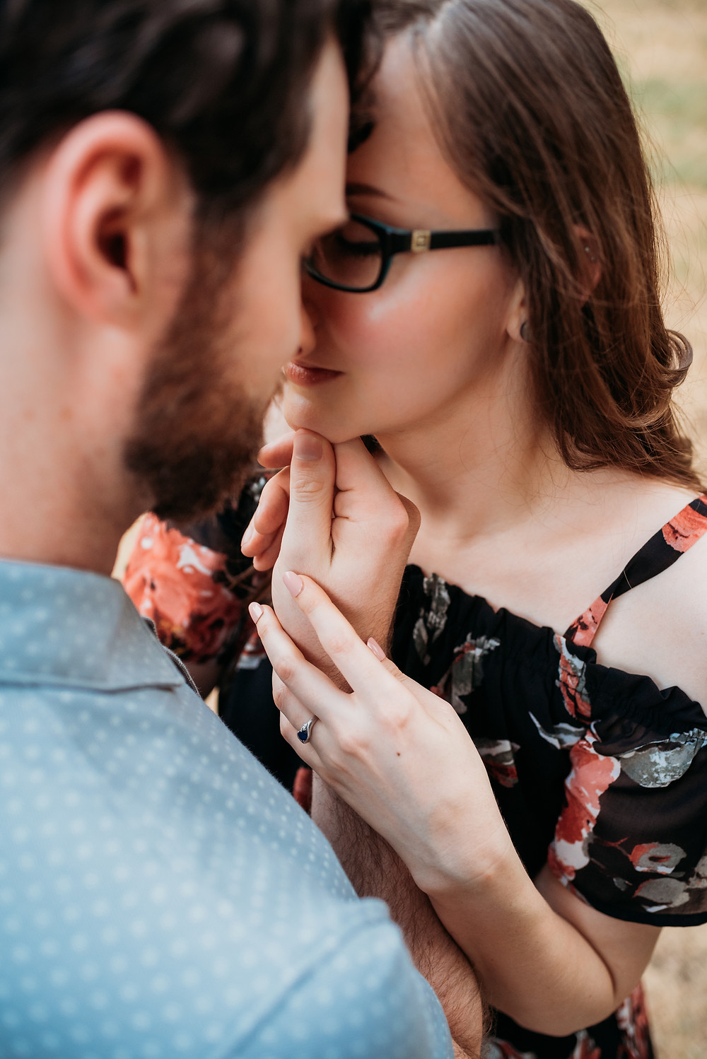 close up photo of a girl and guy standing forehead to forehead. The camera angle is looking down from behind the guy's shoulder. the guy is tilting the girl's face up towards him and the girl has her hand resting on his wrist to show off her engagement ring