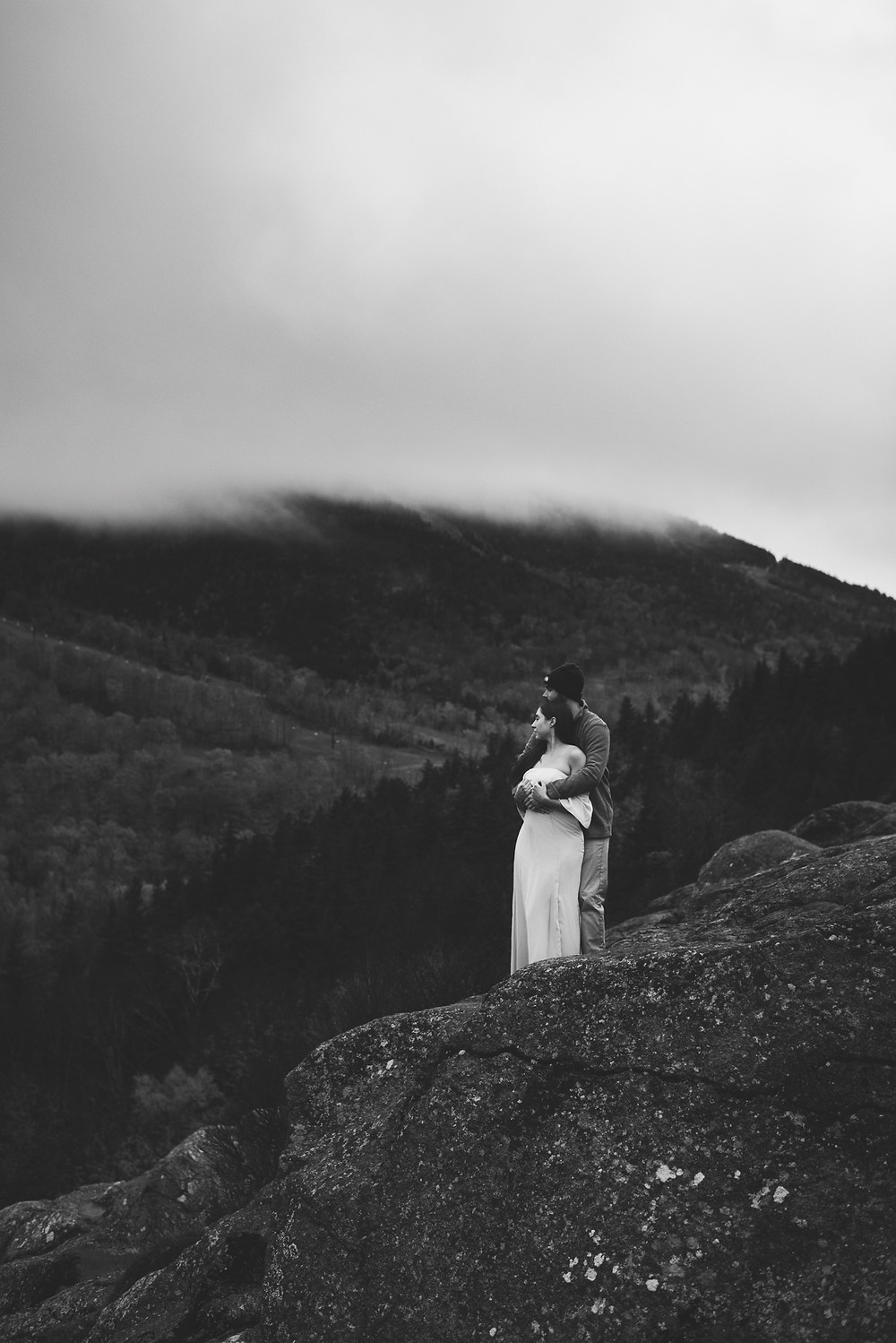 couple stands looking out at view with fog obscuring the top of the mountain in the background. white mountains in new hampshire