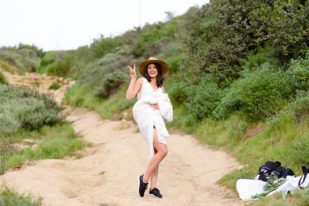 candid photo of bride holding train of dress up and holding up a peace sign to the camera