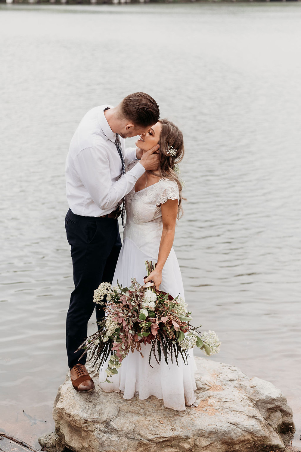bride and groom stand on a rock in lady bird lake for their newlywed portraits during their austin elopement. the groom had the brides face gathered in his hands and she is looking up at him. bride holds bouquet down to her side