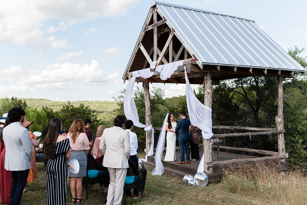 a photo of the wedding ceremony scene. you can see the couple on the alter, the guests standing in attendance, and the view of the hill country. the wedding is at Hill Country Casitas in Dripping Springs, Texas