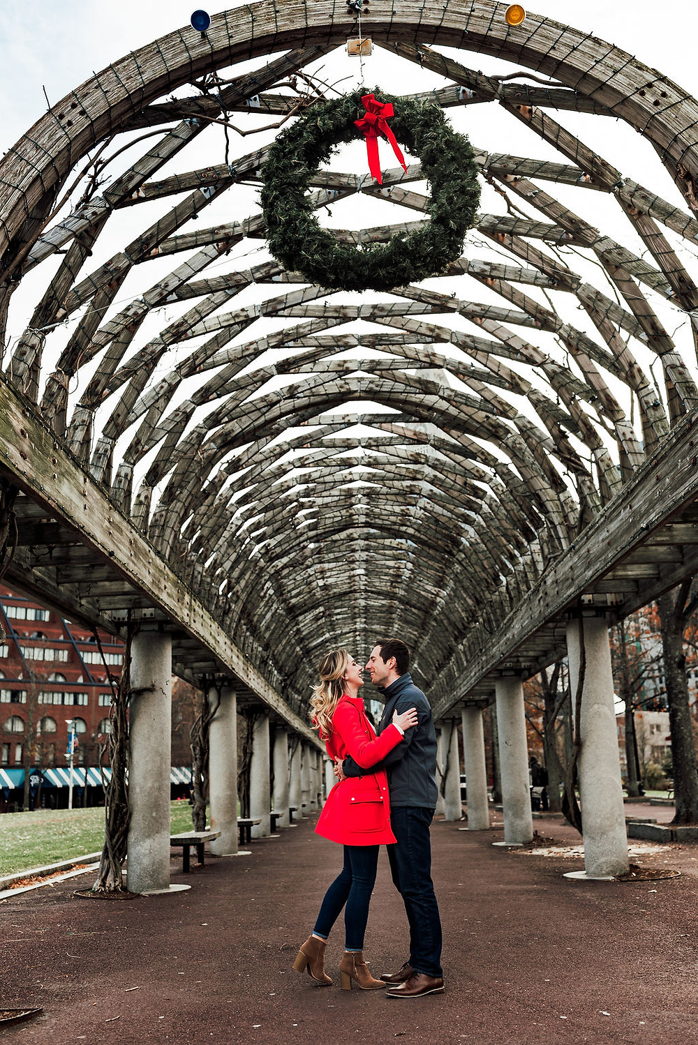 engagement session at christopher columbus park in boston. Coouple is standing under the trellis kissing during a Christmastime. A wreath hangs on the trellis.