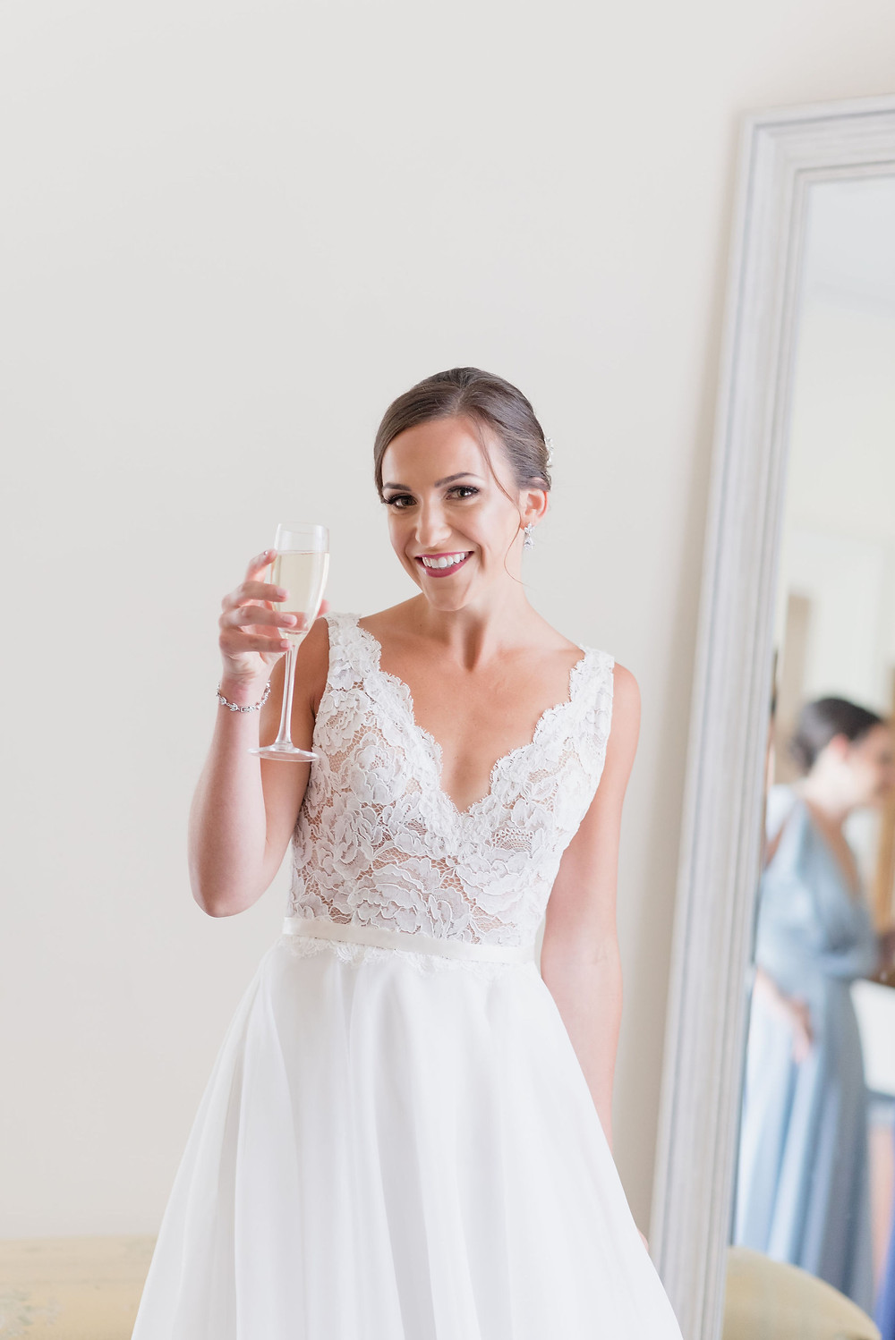 photo of bride smiling at the camera with a champagne class