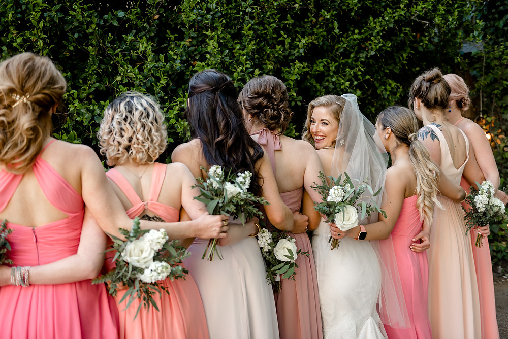 back of bridesmaids with bride turned around smiling