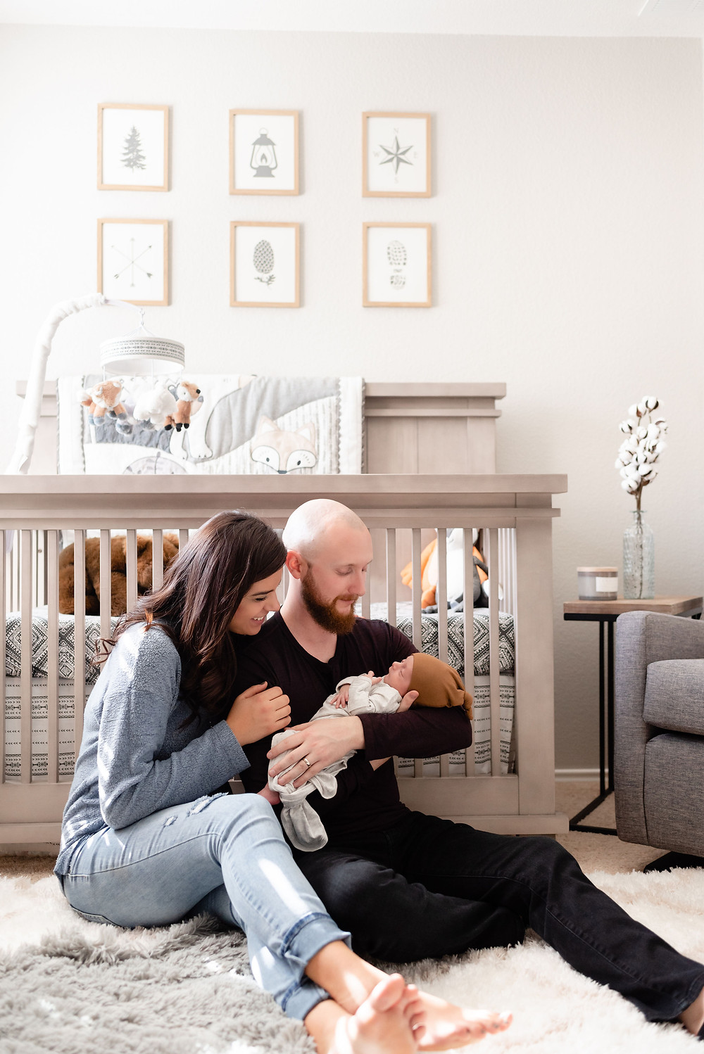 in home newborn session with couple sitting by crib