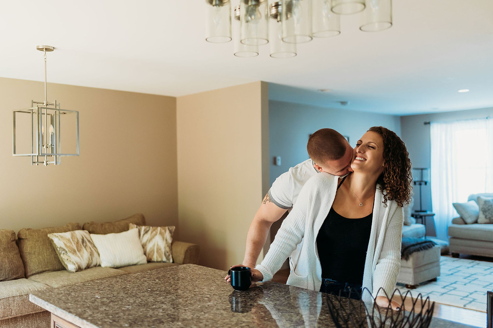 in home engagement session couple stands at kitchen counter with guy behind girl giving her neck kisses