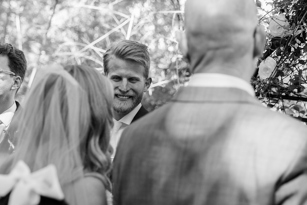groom's face between bride and father's heads as bride walks down aisle at wedding