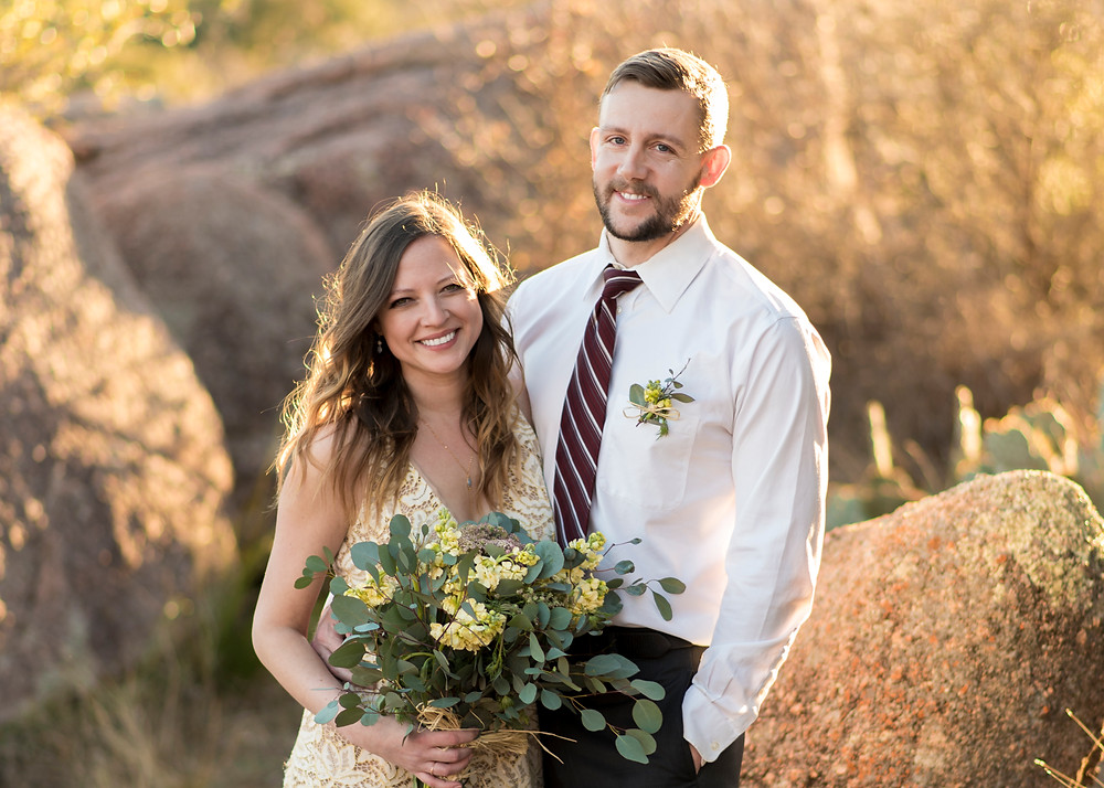 bride and groom smile at the camera during their elopement at enchanted rock