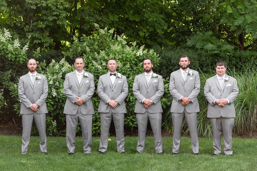 groomsmen looking serious at camera shoulder to shoulder