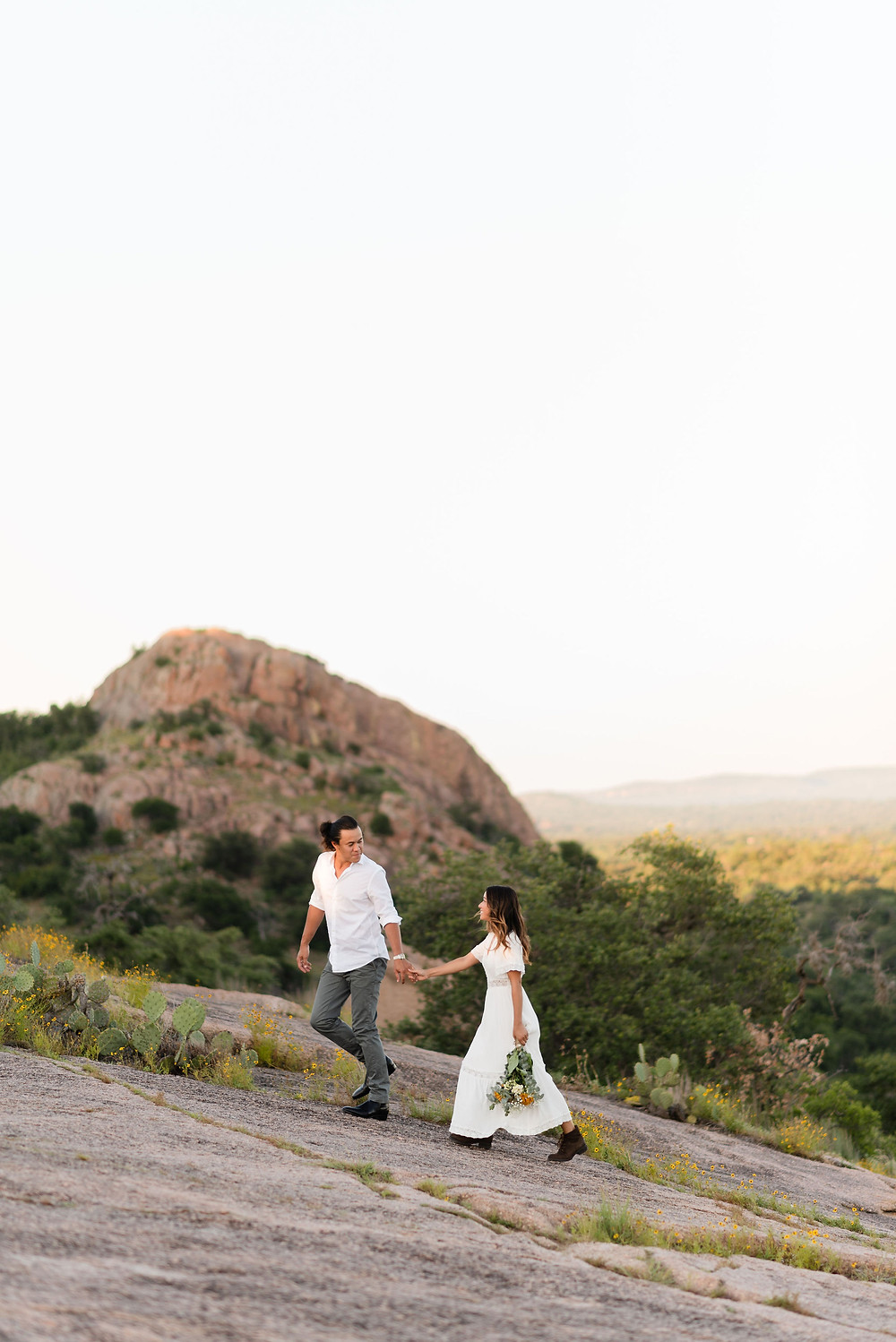 groom leading bride up mountainside at enchanted rock