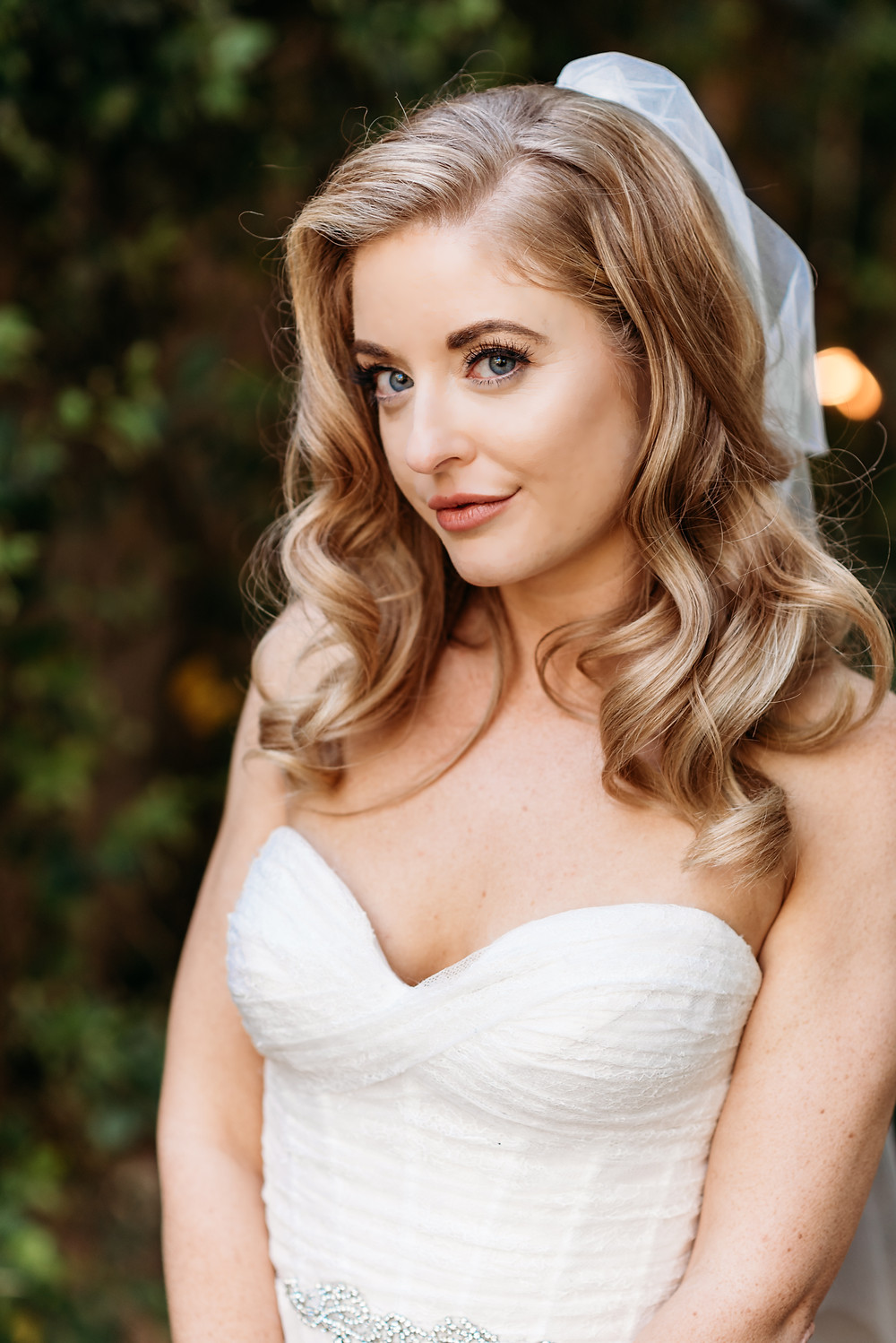 blonde hair blue eye bride looking at camera in her strapless wedding dress and veil