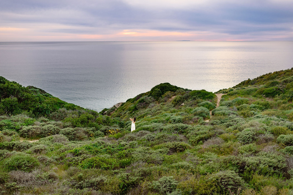 adventurous bridal session - bride on rolling green hills with the pacific ocean and sunset in the background