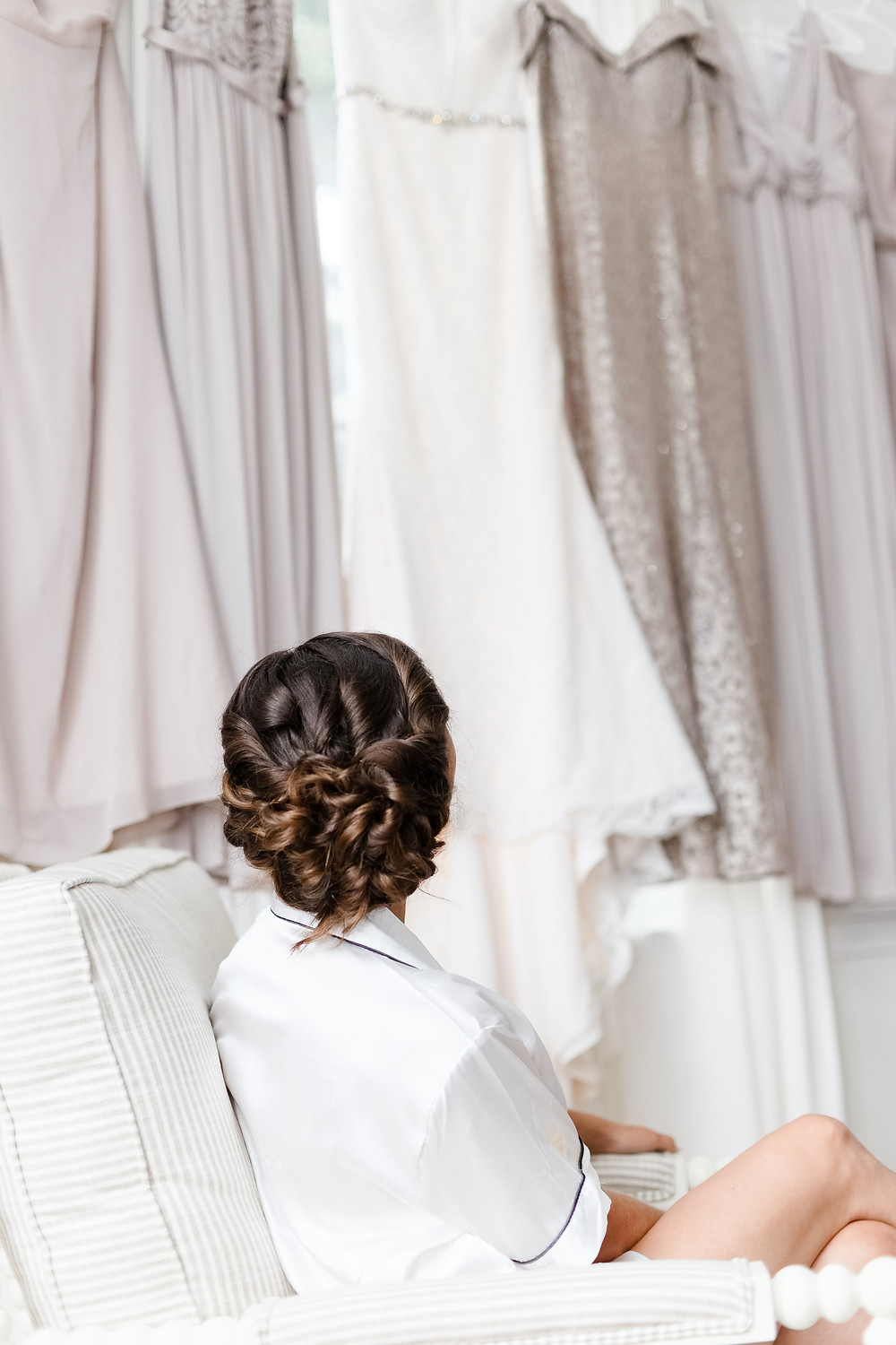 bride looking at wedding dress hanging up
