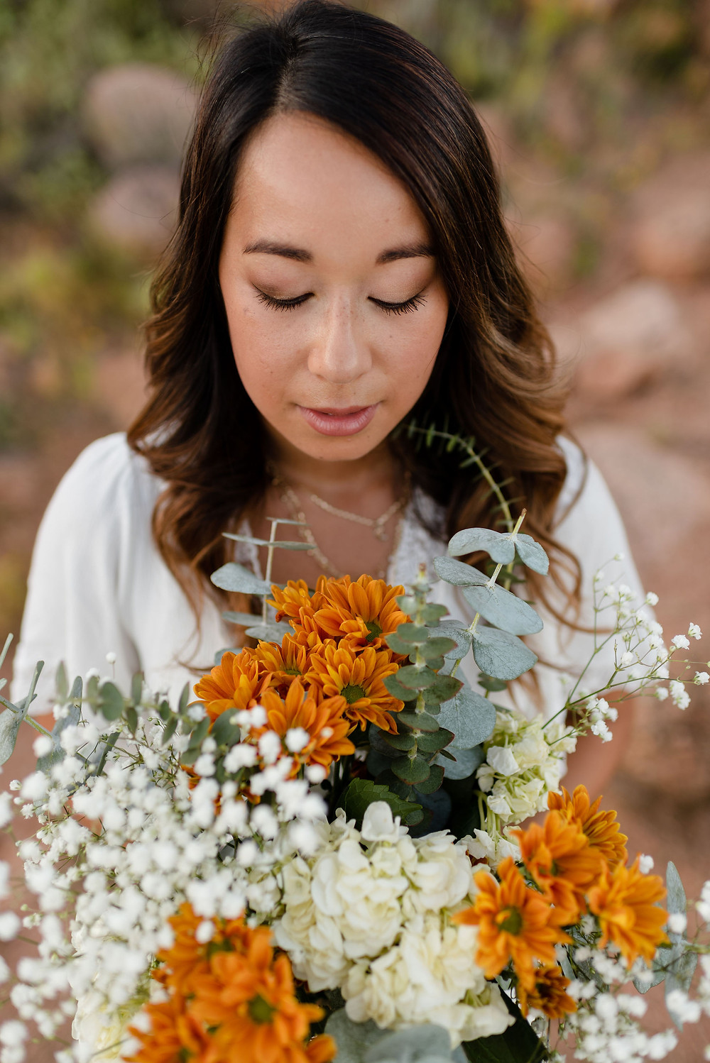 girl looking down at bouquet with white and orange flowers