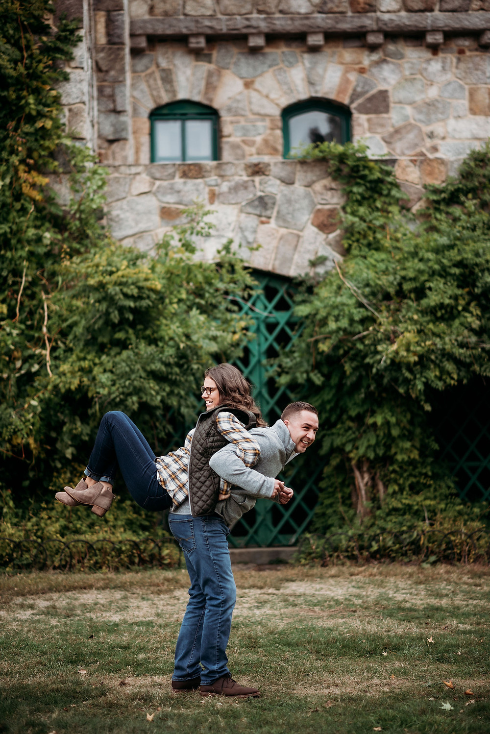 a couple is back to back with their arms interlocked. the guy is bent forward, with the girl's feet off the ground leaning on the guy