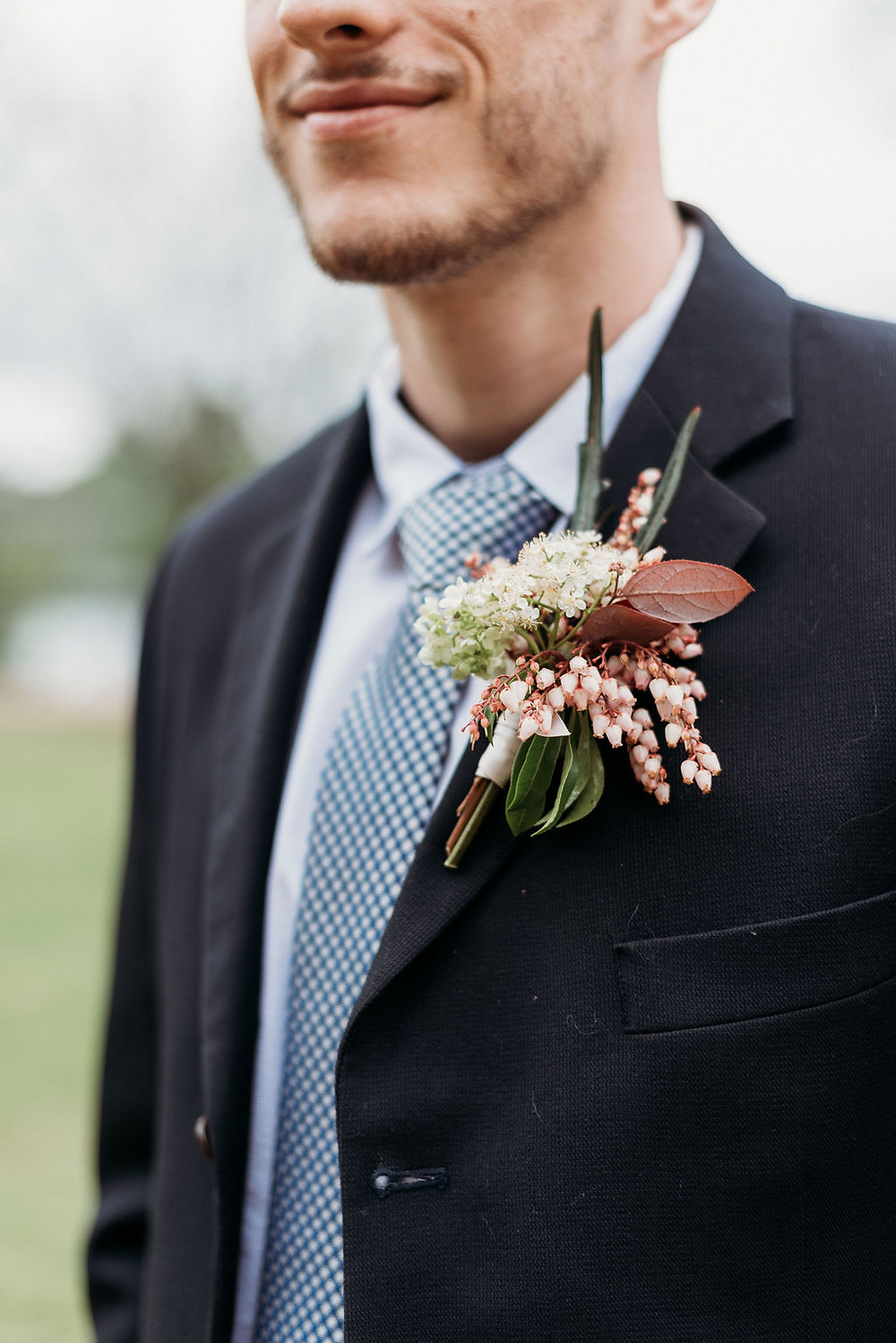 detail photo of groom's details for his Austin elopement. photo is of the groom's boutonnière from wow factor floral. you cannot see the groom's face, just the bottom half of his head so you can see his smile down to mid-torso