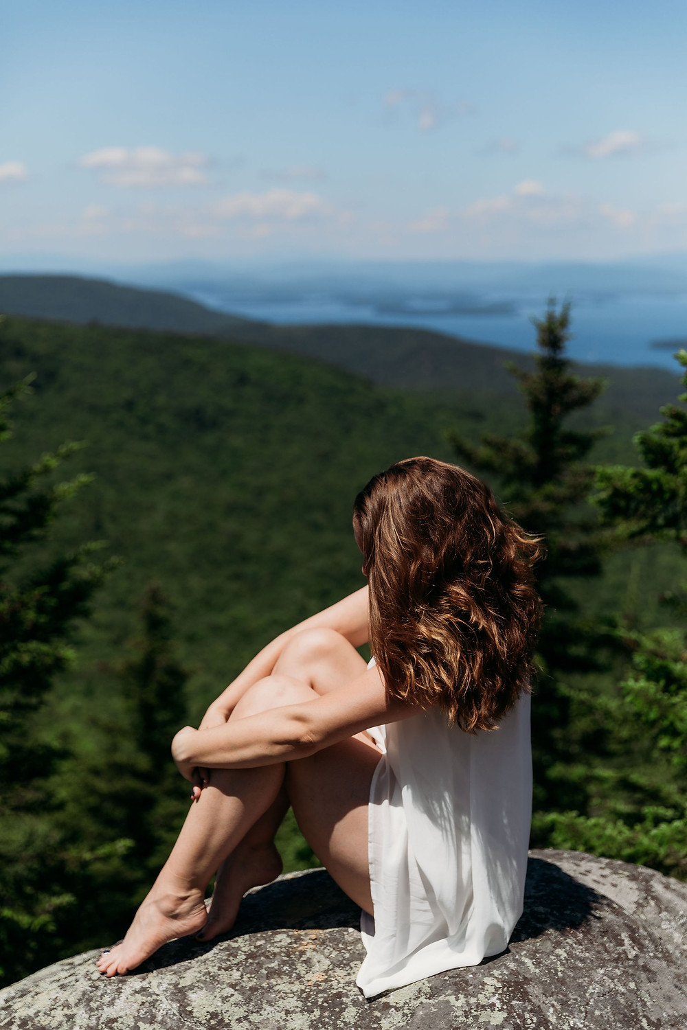 bride sitting on rock on mountain. hair is covering brides face. posed pretty sitting photo