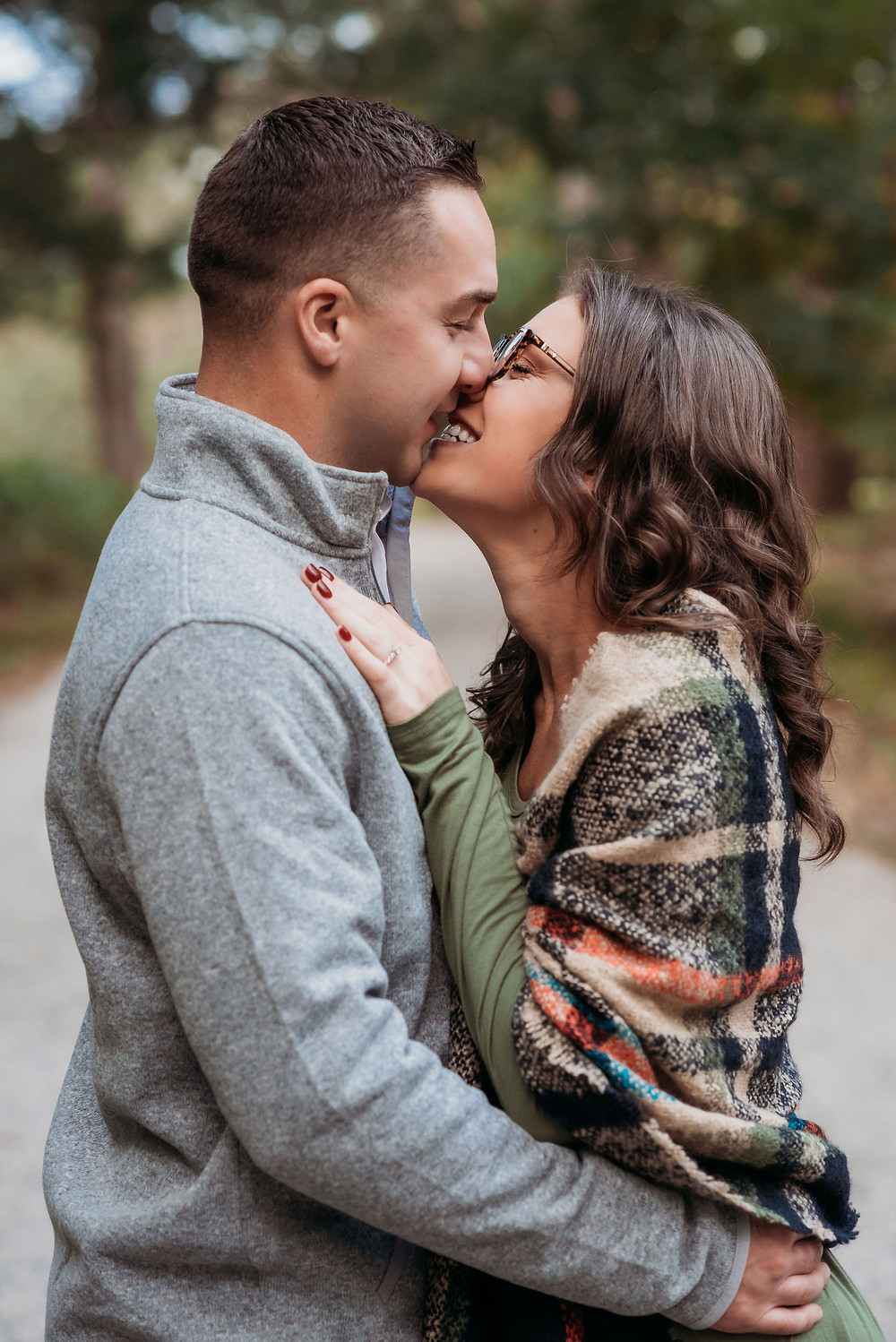 guy and girl stand with their heads very close together, big smiles, almost kissing