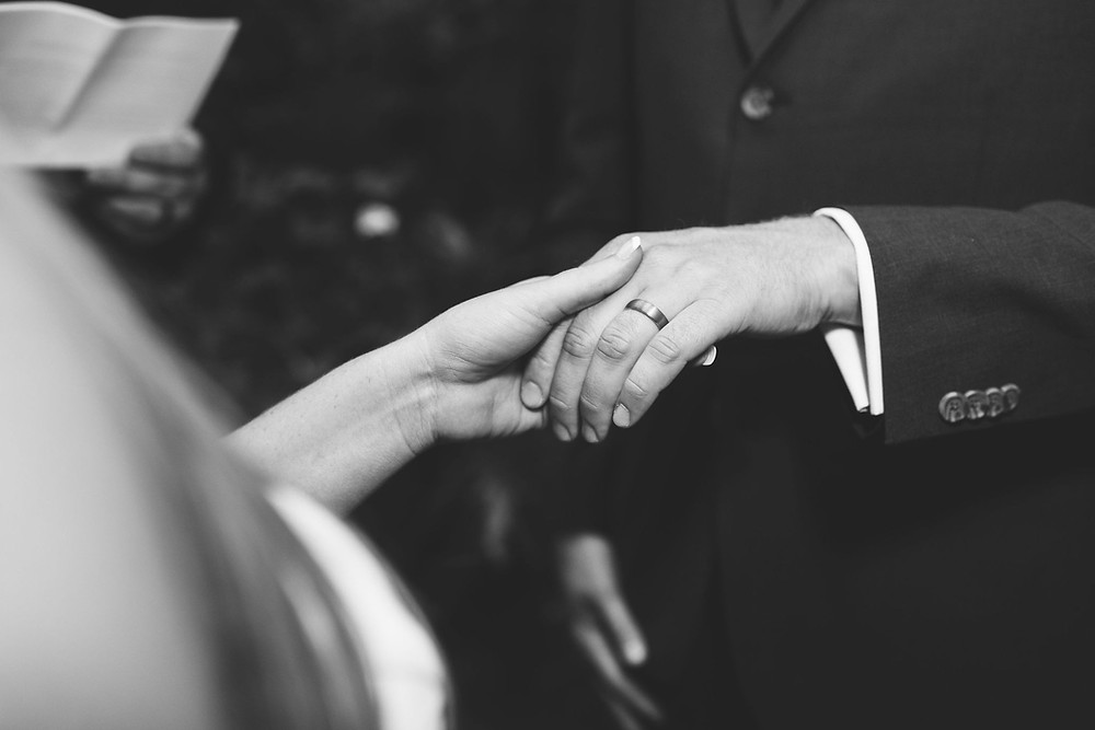 close up photo of bride holding groom's hand after ring exchange, groom wearing wedding ring