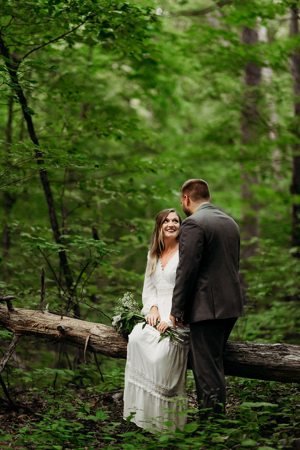 bride sitting down on a fallen tree trunk. groom stands next to her. they look into each other's eyes.