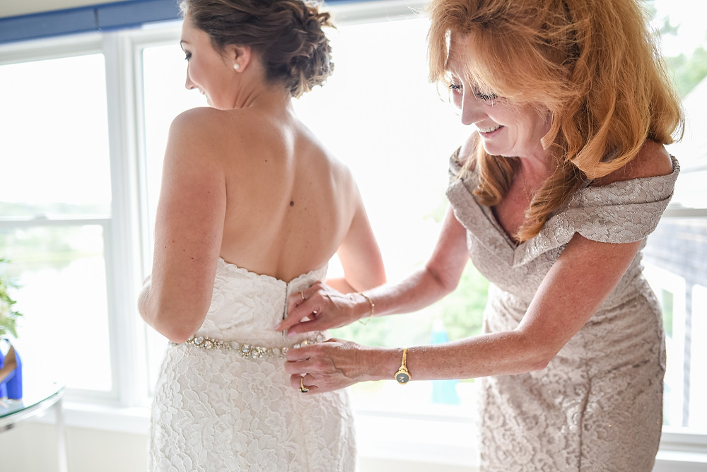 mom putting on bride's wedding dress